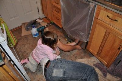 Ella helps dad install the dishwasher