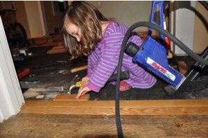Ella helps install flooring.